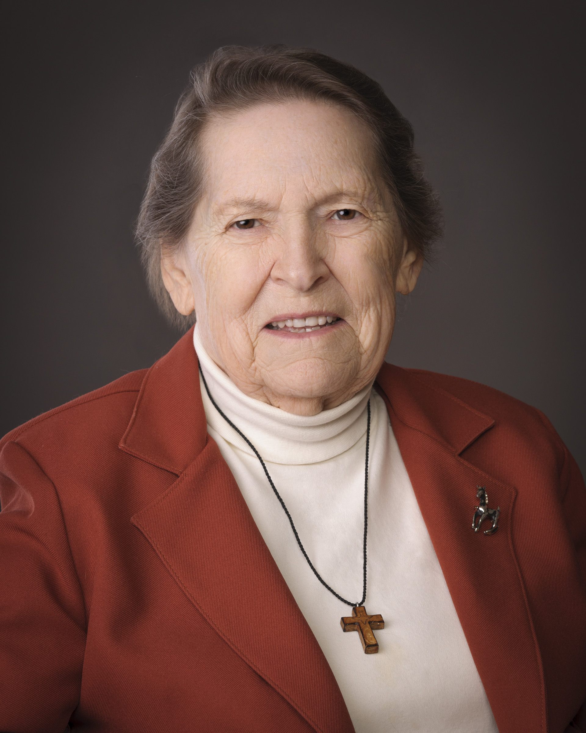 Anne Barton with a red suit jacket and white turtleneck. There is a wooden cross around her neck